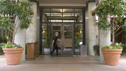 doorman opening door for guests - receptionist stock videos & royalty-free footage