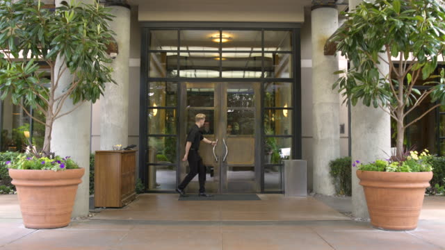 doorman opening door for guests - hotel stock-videos und b-roll-filmmaterial