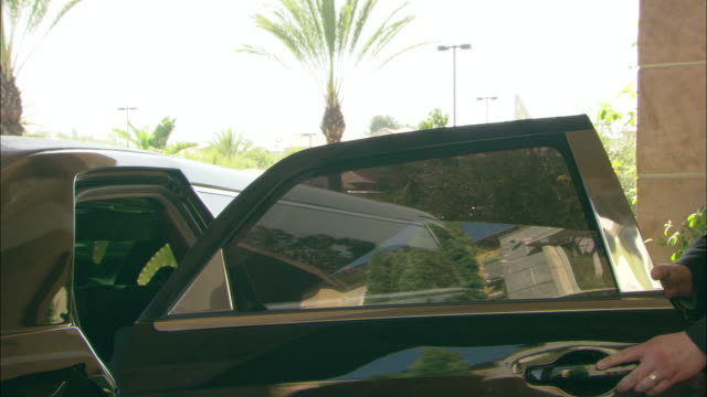 a doorman opens the door to a limousine for a young woman and steps back as the limo drives away. - limousine stock videos & royalty-free footage