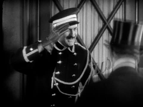 cu, b&w, doorman saluting to man, getting tip, 1920's  - 敬礼点の映像素材/bロール