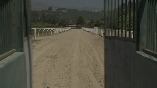 doors of a starting gate swing open, revealing a racehorse track. - starting gate stock videos and b-roll footage