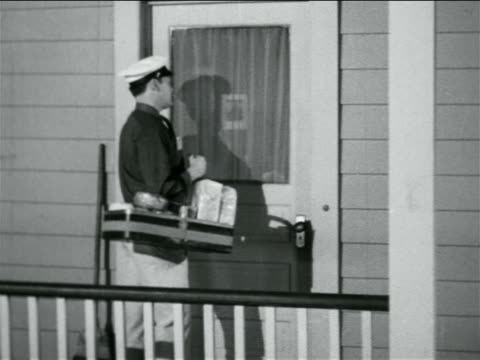 b/w 1938 door-to-door bakery salesman talking to housewife at door of house / industrial - salesman stock videos and b-roll footage