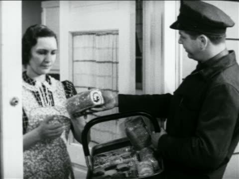 b/w 1938 door-to-door salesman handing housewife jellyroll from basket / industrial - door to door salesperson stock videos & royalty-free footage