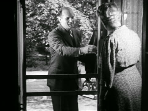 B/W 1946 door-to-door salesman opens screen door and shows vacuum cleaner to the lady of the house