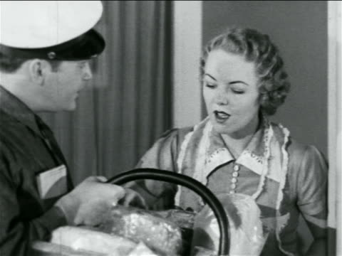 stockvideo's en b-roll-footage met b/w 1938 door-to-door salesman showing housewife basket of baked goods / industrial - 1938