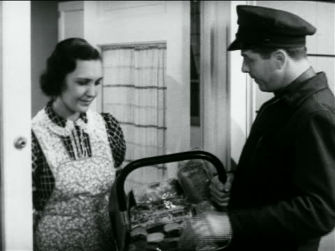 b/w 1938 door-to-door salesman showing housewife basket of baked goods / industrial - doorway stock videos & royalty-free footage