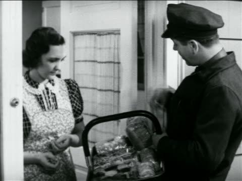 b/w 1938 door-to-door salesman showing housewife basket of baked goods / industrial - türrahmen stock-videos und b-roll-filmmaterial