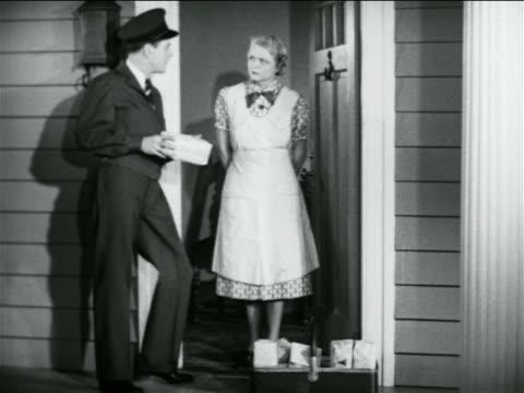 b/w 1938 door-to-door salesman talking to housewife in doorway + pointing to ground / industrial - door to door salesperson stock videos & royalty-free footage