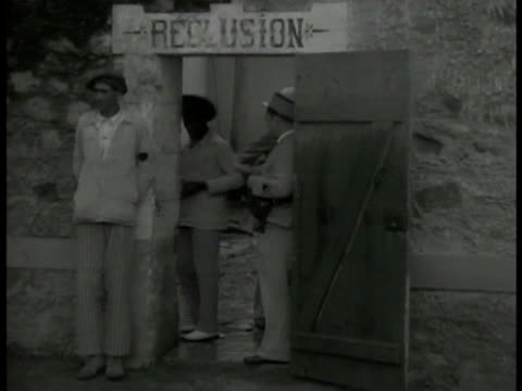 vidéos et rushes de doorway sign: 'reclusion', guard standing in doorway, pushing prisoner back. int long line of doors w/ trustee filling extended cups from doors w/... - dom tom