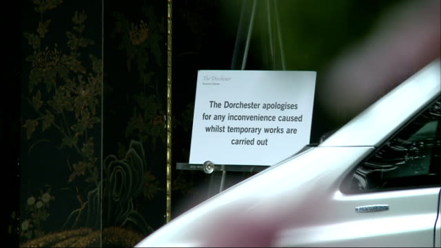 dorchester hotel victim of second robbery in a month; england: london: ext 'the dorchester' sign with flowers underneath notice on easel apologising... - dorchester hotel stock videos & royalty-free footage