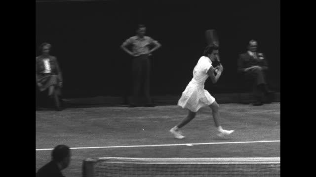 doris hart serves ball into net at wimbledon for 1951 singles final against shirley fry irvin, ball boy retrieves ball, hart serves again, returns... - 決勝戦点の映像素材/bロール