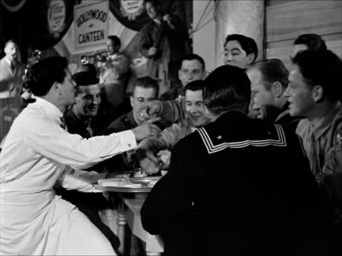 vídeos de stock, filmes e b-roll de doris merrick brenda joyce sitting together laughing john garfield serving servicemen at table robert benchley behind bar joined by charles... - 1943