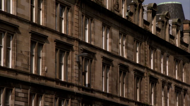 dormers line the roof of a building in glasgow scotland. available in hd. - dacherker stock-videos und b-roll-filmmaterial