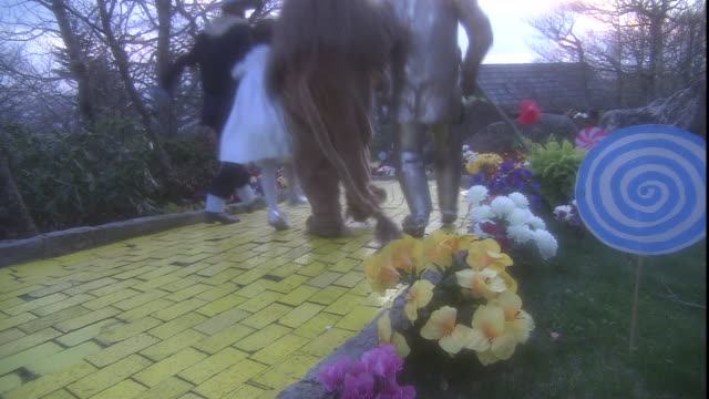 vídeos y material grabado en eventos de stock de dorothy, the tin man, the scarecrow, and the cowardly lion skip down the yellow brick road. - fantasía