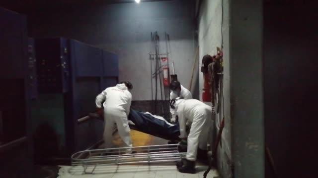dos operarios bajan de la carroza el cuerpo de ramiro envuelto en una bolsa azul y lo conducen al horno - azul stock videos & royalty-free footage