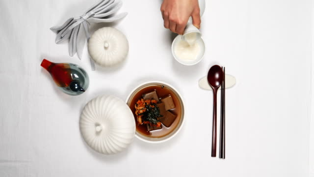 'dotorimukbap' (rice with acorn jelly in cold broth) and 'sanseong makgeolli' - table top shot stock videos & royalty-free footage