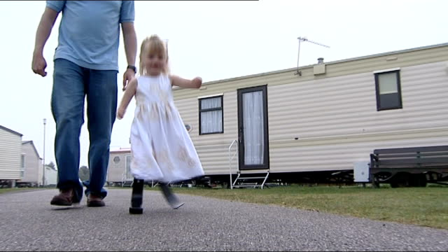 Double amputee Ellie Challis learns to walk using carbonfibre blades ENGLAND Essex Little Clacton Ellie along on blades with her father