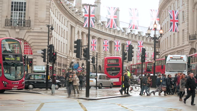 Double decker bus drives by and pedestrians cross street at Piccadilly Circus.