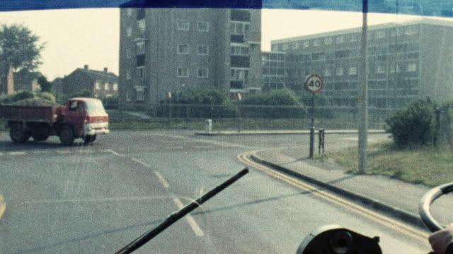 1974 montage double decker bus driving in traffic / southampton, hampshire, england - イングランド サウサンプトン点の映像素材/bロール
