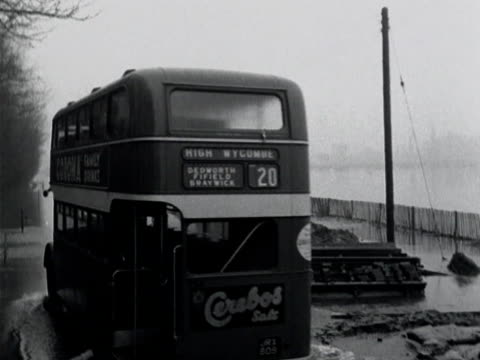 a double decker bus moves along a flooded road - double decker bus stock videos & royalty-free footage