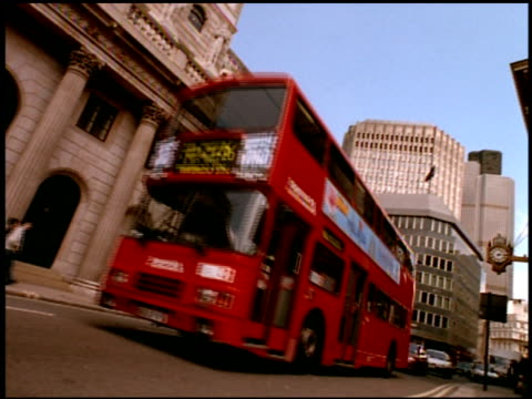 Double decker bus passes along street, London