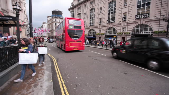 double decker bus passes by a busy london street corner. - autobus a due piani video stock e b–roll