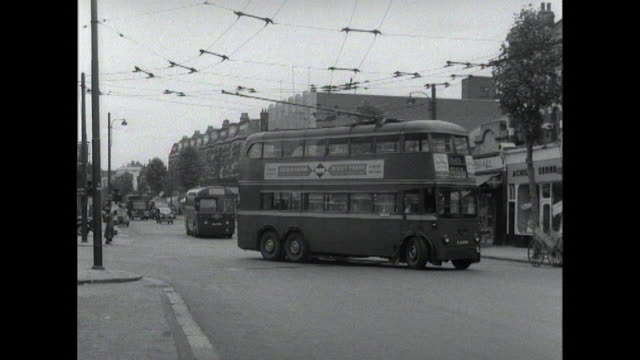 a double decker bus travels along a street in london - autobus a due piani video stock e b–roll