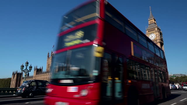 Double decker buses and other traffic pass Big Ben and Houses of Parliament in London.