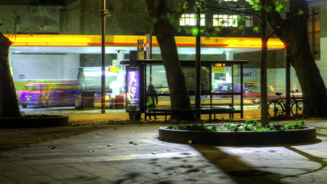 Double deckers stream with traffic past a bus stop and petrol station in a time lapse of London, England at night.