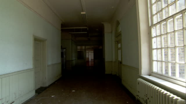 vidéos et rushes de double doors at the end of a bright white corridor lead to a wing of high royds psychiatric hospital. available in hd. - hôpital psychiatrique