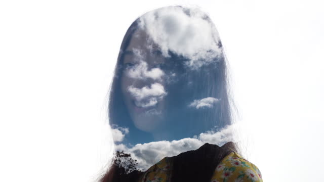Double exposure of woman looking clouds