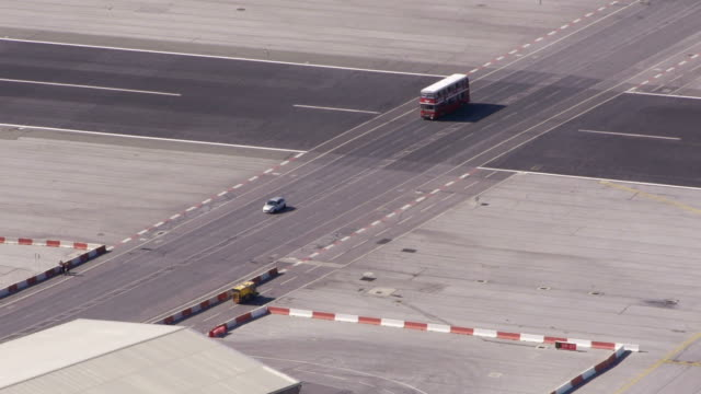double-decker bus and airport vehicles on airstrip of gibralta - gibraltar bildbanksvideor och videomaterial från bakom kulisserna