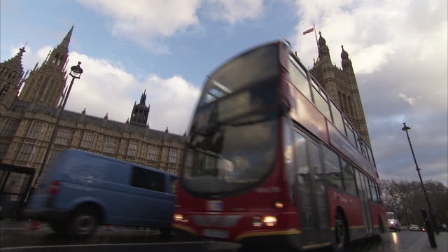 A double-decker bus passes below Victoria Tower at the Palace of Westminster in London. Available in HD.