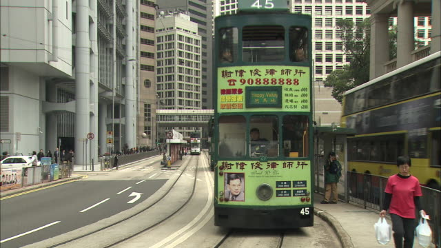 vídeos de stock e filmes b-roll de double-decker buses cruise through a business district. - linha do elétrico