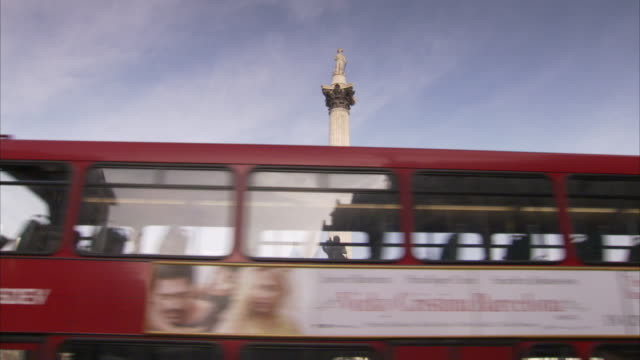 double-decker buses pass nelson's column and the statue of charles i on trafalgar square. - nelson's column stock videos and b-roll footage