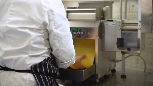 dough rolled through large pasta machine - pasta machine stock videos and b-roll footage