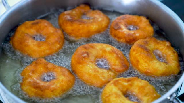 ドーナツを油で揚げてください。 - 調理用へら類点の映像素材/bロール