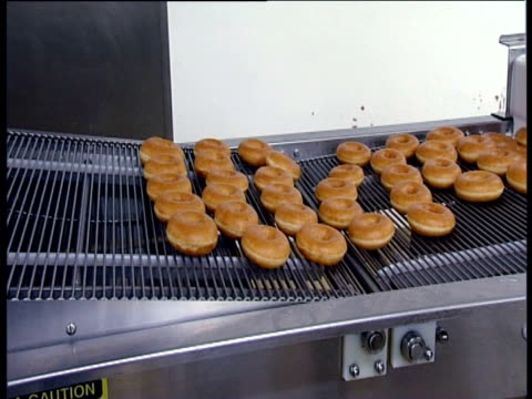 doughnuts passing through glazing machine and emerging at end of process - doughnut stock videos and b-roll footage