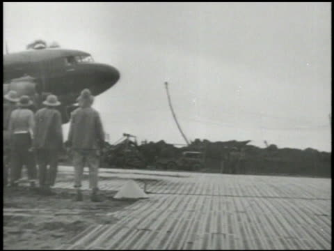 Douglas C47 Skytrain taxiing on airstrip after landing unidentified female deplaning group of US Marines greeting excited female signing autographs...