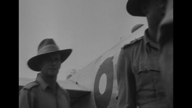 a douglas c54 skymaster transport airplane taxis at nichols field / british and americans shake hands / british officer with a mustache he salutes... - limousine familienfahrzeug stock-videos und b-roll-filmmaterial