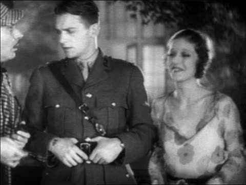 B/W 1931 Douglas Fairbanks, Jr. in uniform + Loretta Young talking with detective / feature