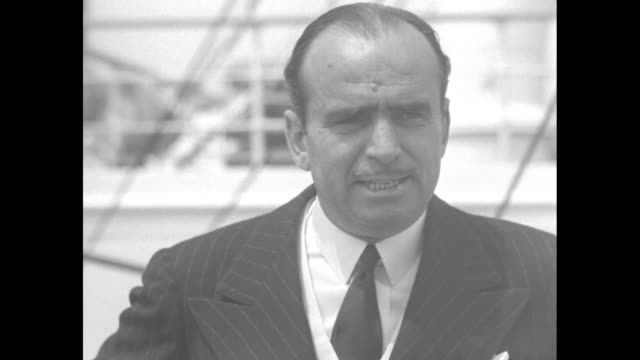 Douglas Fairbanks Sr wearing suit and tie stands on ship deck neatly leaps over railing and attached life preserver reading 'RMS Aquitania Cunard...