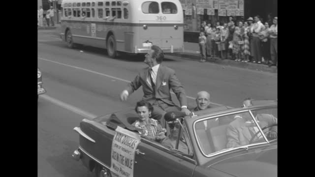 douglas points finger and nods his head while riding on a convertible in a paradeæ - kirk douglas actor stock videos & royalty-free footage