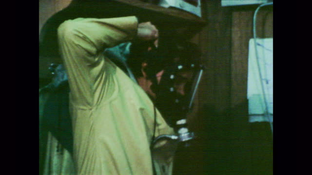 vídeos de stock e filmes b-roll de 1978 dow chemical worker in safety clothing attaches respirator to his face mask as other workers take a shower - the dow chemical company