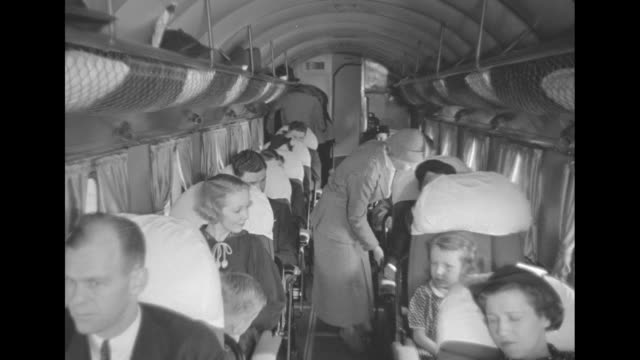 """vídeos de stock, filmes e b-roll de down aisle of """"transcontinental & western air"""" airplane interior as flight attendant in long-skirted uniform attends to passengers at rear, woman and... - avião comercial"""