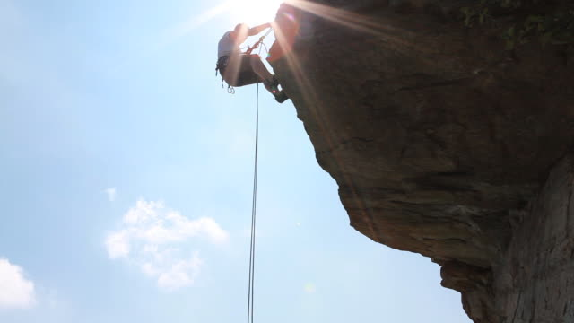 pan down as climber rappels (abseils) from overhanging rock - abseiling stock videos & royalty-free footage