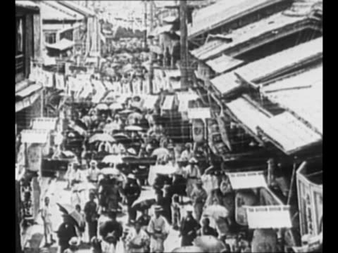 ls down busy street packed with pedestrians in 1920s japan / citizens walk in boardwalktype area / ms roofs of houses before the 1923 earthquake /... - 1920年点の映像素材/bロール