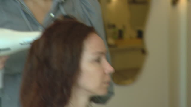 pan down ws of drybar r/f woman getting her hair done cu stylist blow drying hair cu client with wet hair ms stylist and client pan to stylist... - blow drying hair stock videos and b-roll footage