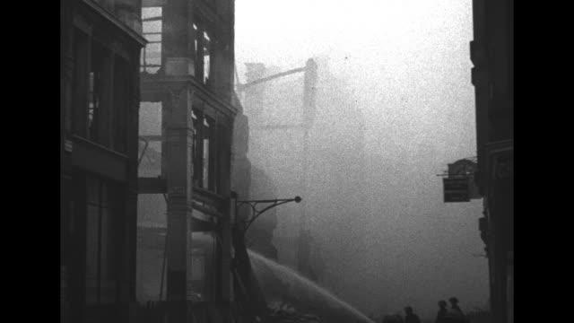 pan down exterior of skeletal church with broken windows / fire hoses spraying water on smoldering rubble which creates smoke pan across interior of... - bombardamento video stock e b–roll