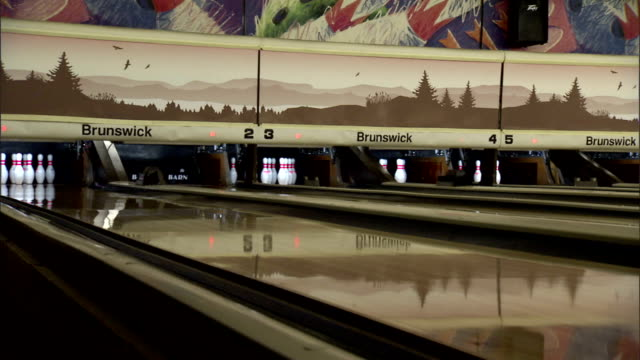 down lane toward pins green bowling ball moving down slick surface of lane toward pins knocking over all but 1 pin automatic pinsetter starting to... - bowling ball stock videos & royalty-free footage